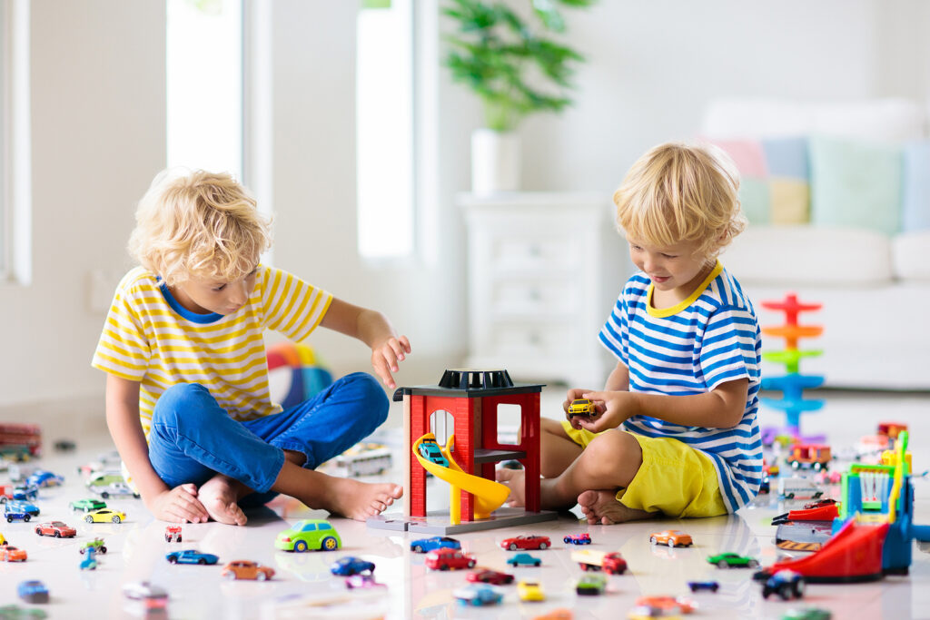 Kids play with toy cars in white room. Little boy playing with car and truck toys. Vehicle and transportation game for children. Kid with parking garage. Child having fun at home or daycare.